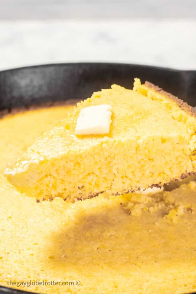 Cornbread topped with butter being served out of a cast iron skillet.