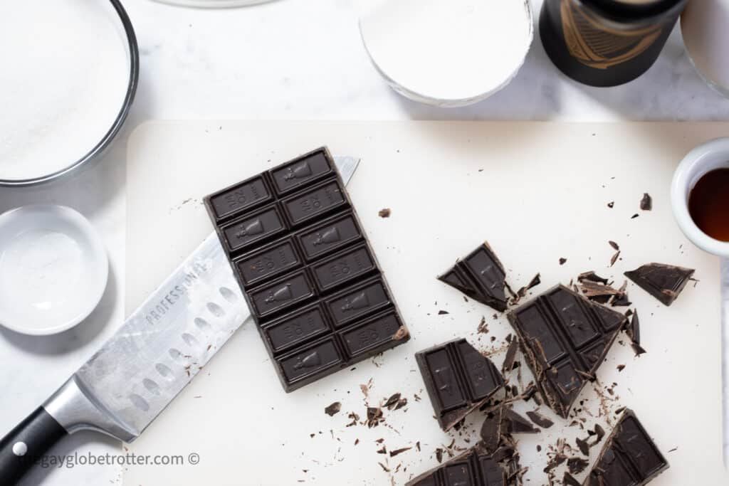 Dark chocolate being chopped on a cutting board.