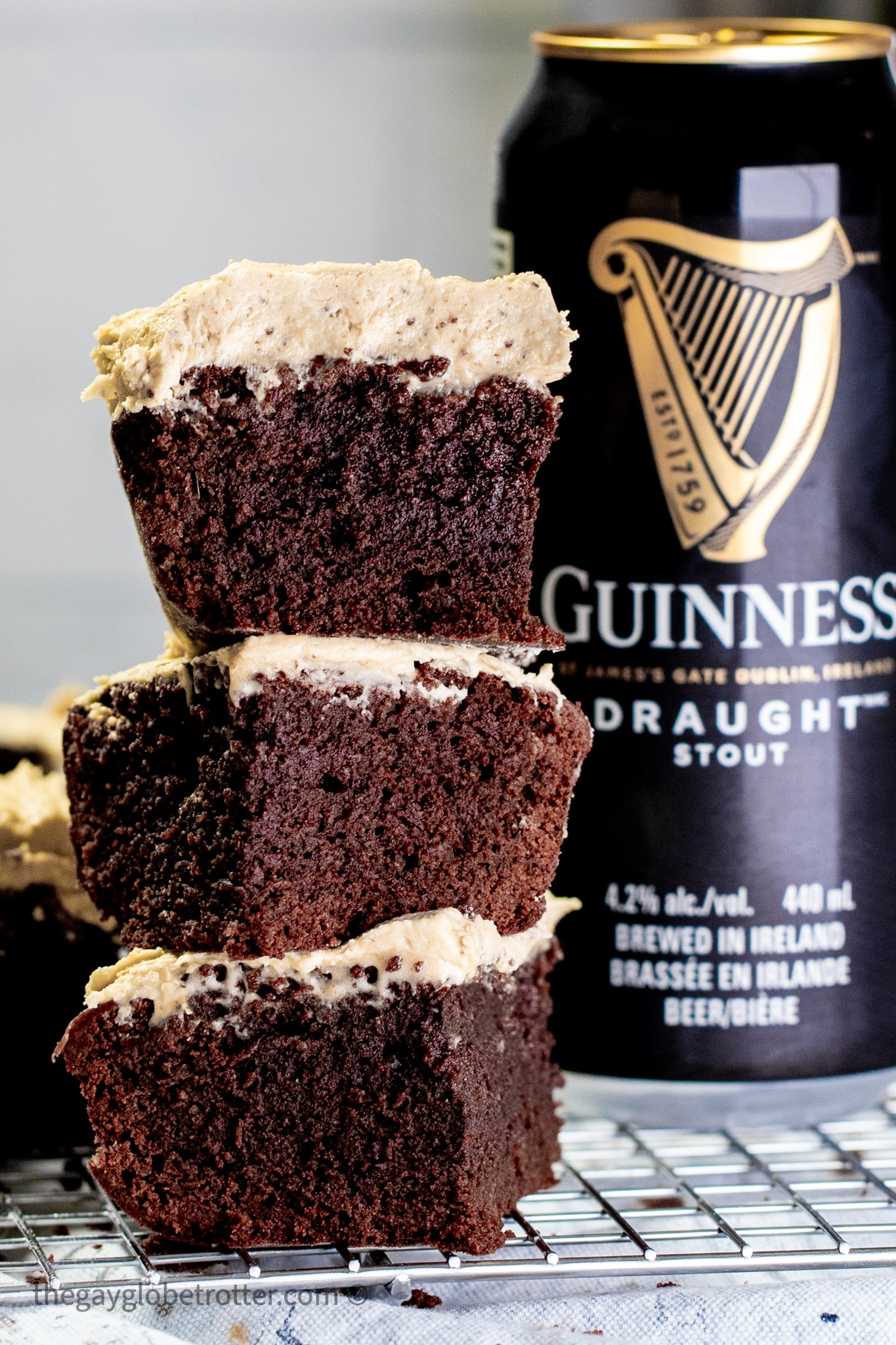 Guinness brownies with icing stacked next to a can of beer.