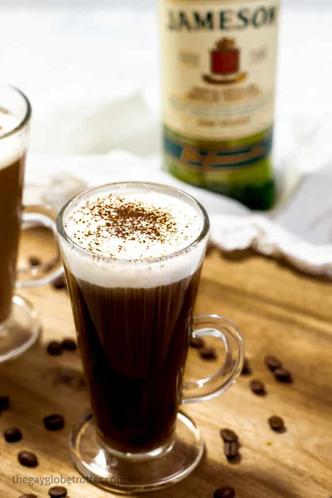 Irish coffee topped with powdered sugar next to coffee beans.