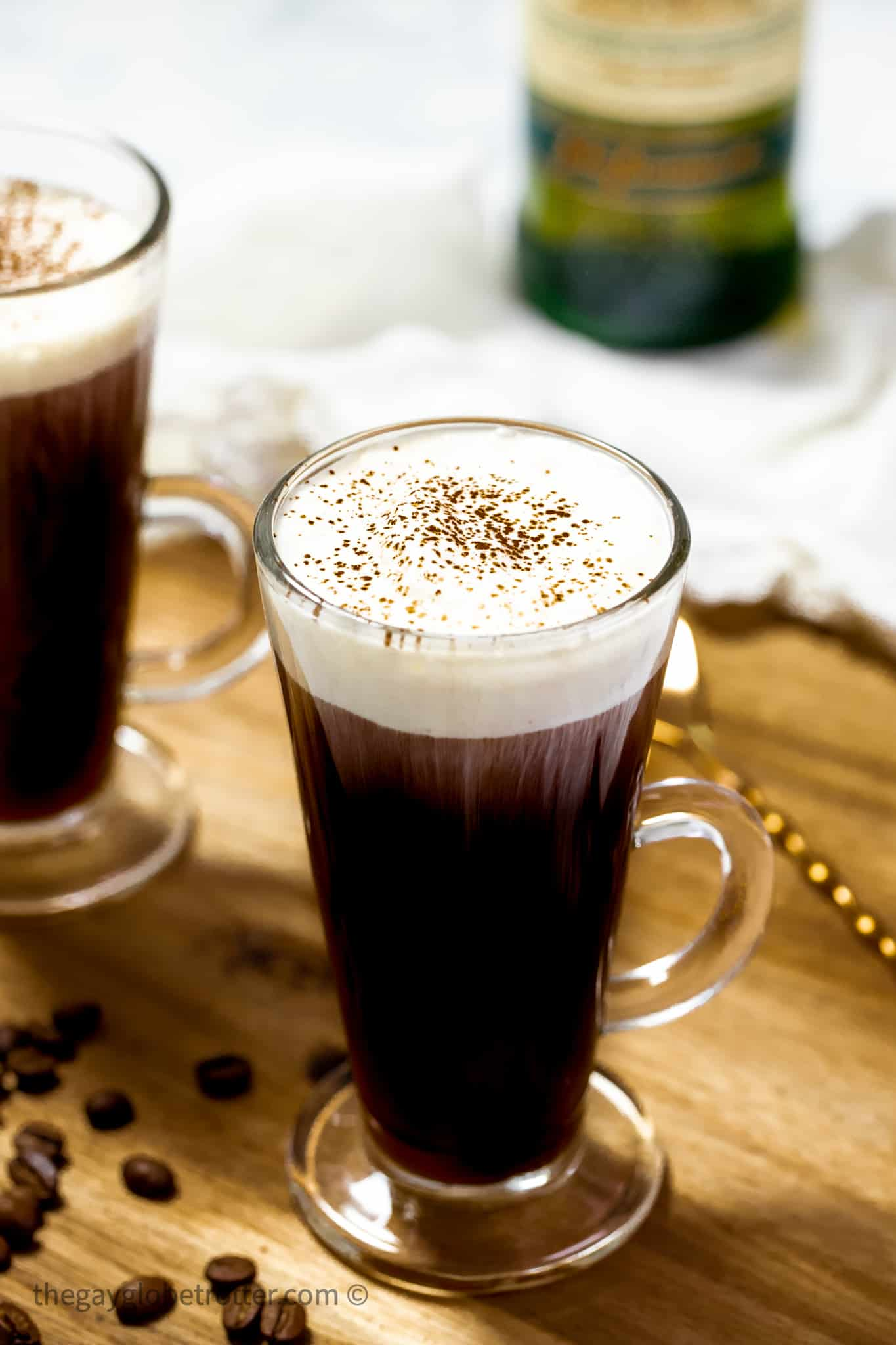 2 cups of Irish coffee next to a stirring spoon.