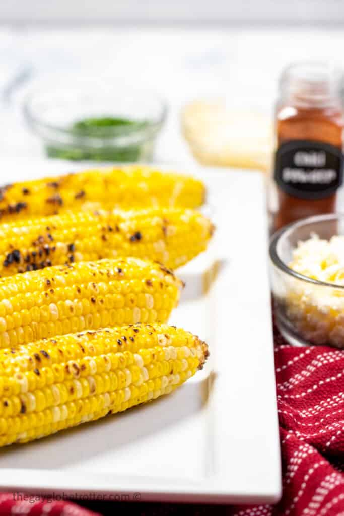 Grilled corn on a working surface with cilatnro.