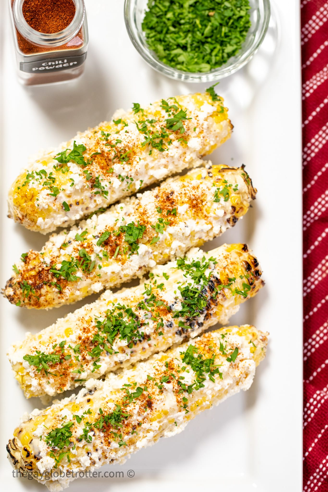 Mexican street corn on a plate with cilantro and chili powder.