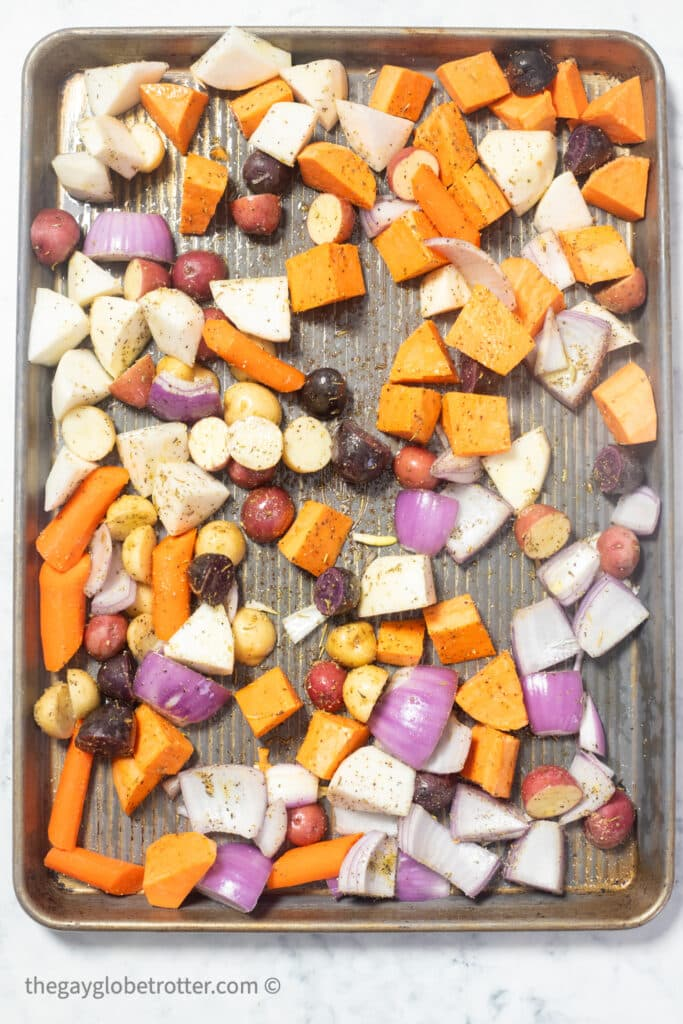 Raw root vegetables on a baking sheet ready to roast.
