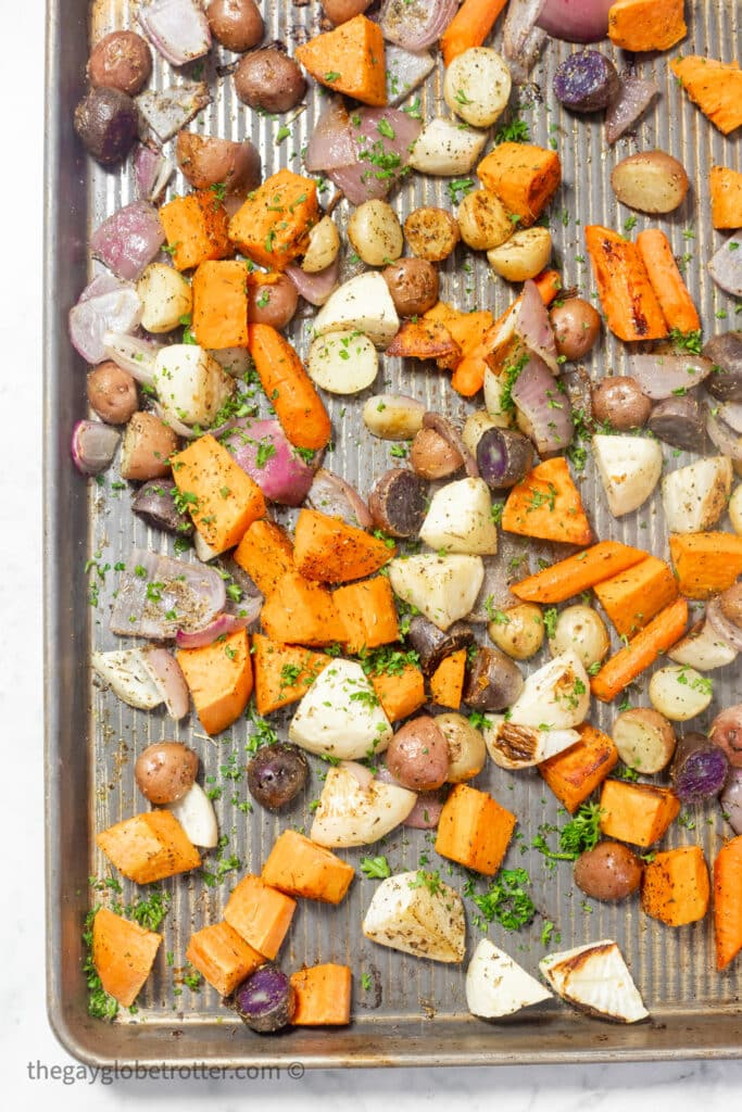 Roasted root vegetables garnished with parsley on a baking sheet.
