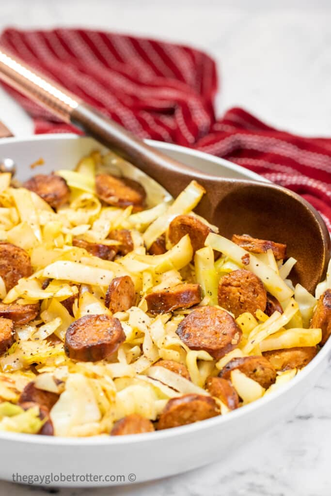 Cabbage and sausage in a skillet with a serving spoon.