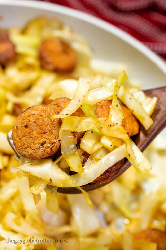 A spoon serving fried cabbage and sausage.