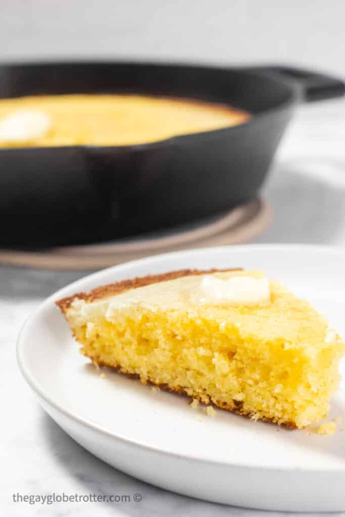 A slice of cornbread on a white plate.