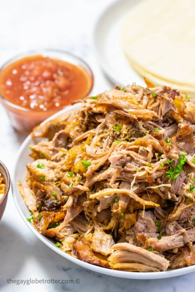 A serving platter of slow cooker pork carnitas with parsley.