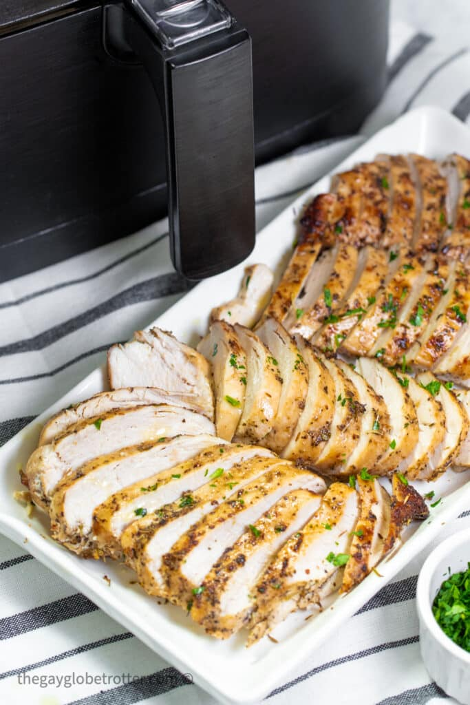 Sliced chicken breasts on a serving tray in front of an air fryer.