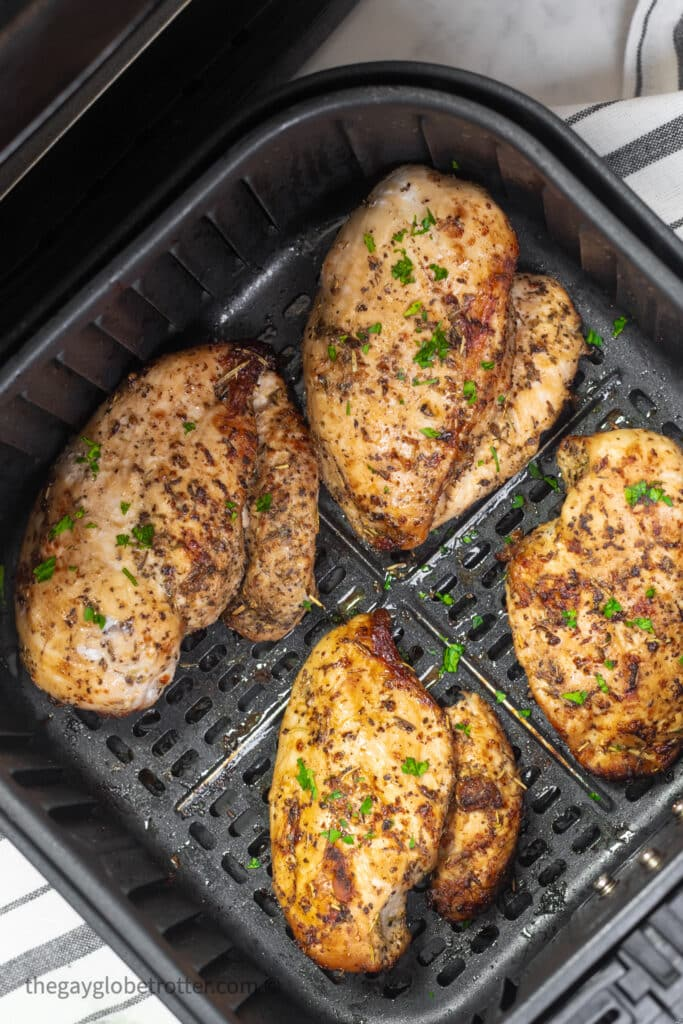 Chicken breasts being flipped in an air fryer.