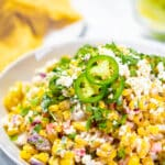 Mexican street corn on a serving plate garnished with cilantro with text overlay.
