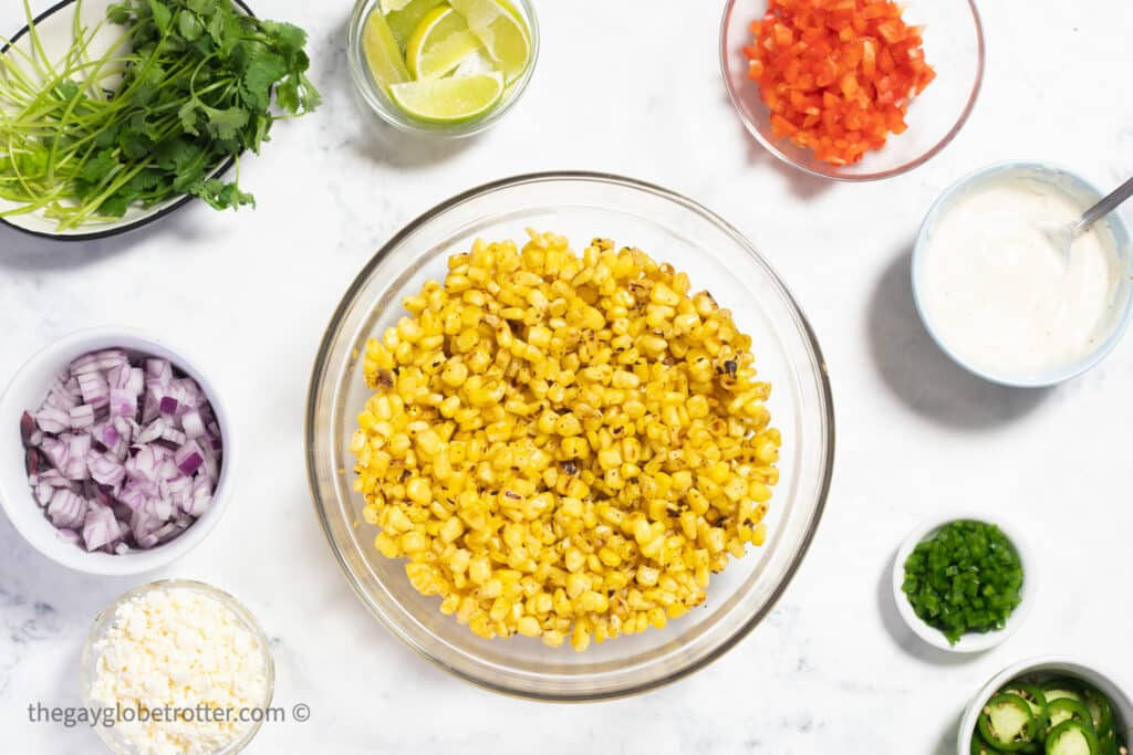 Mexican street corn dip ingredients like corn, red onions, cilantro, and red peppers in bowls.
