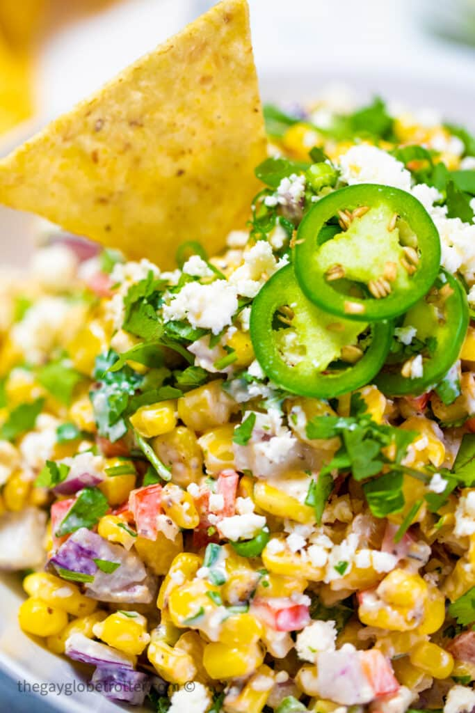 Mexican street corn dip garnished with a tortilla chip and jalapenos.