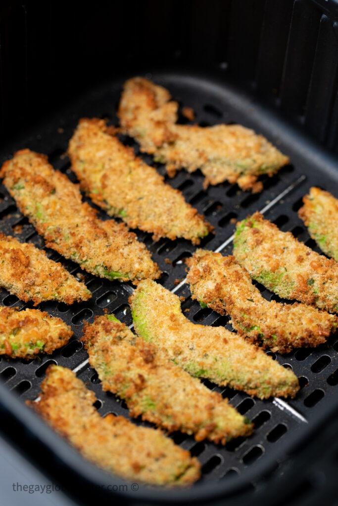Avocado fries in an air fryer basket.