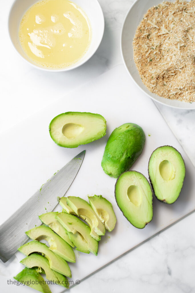 Avocados being cut next to breadcrumbs and egg mixture.