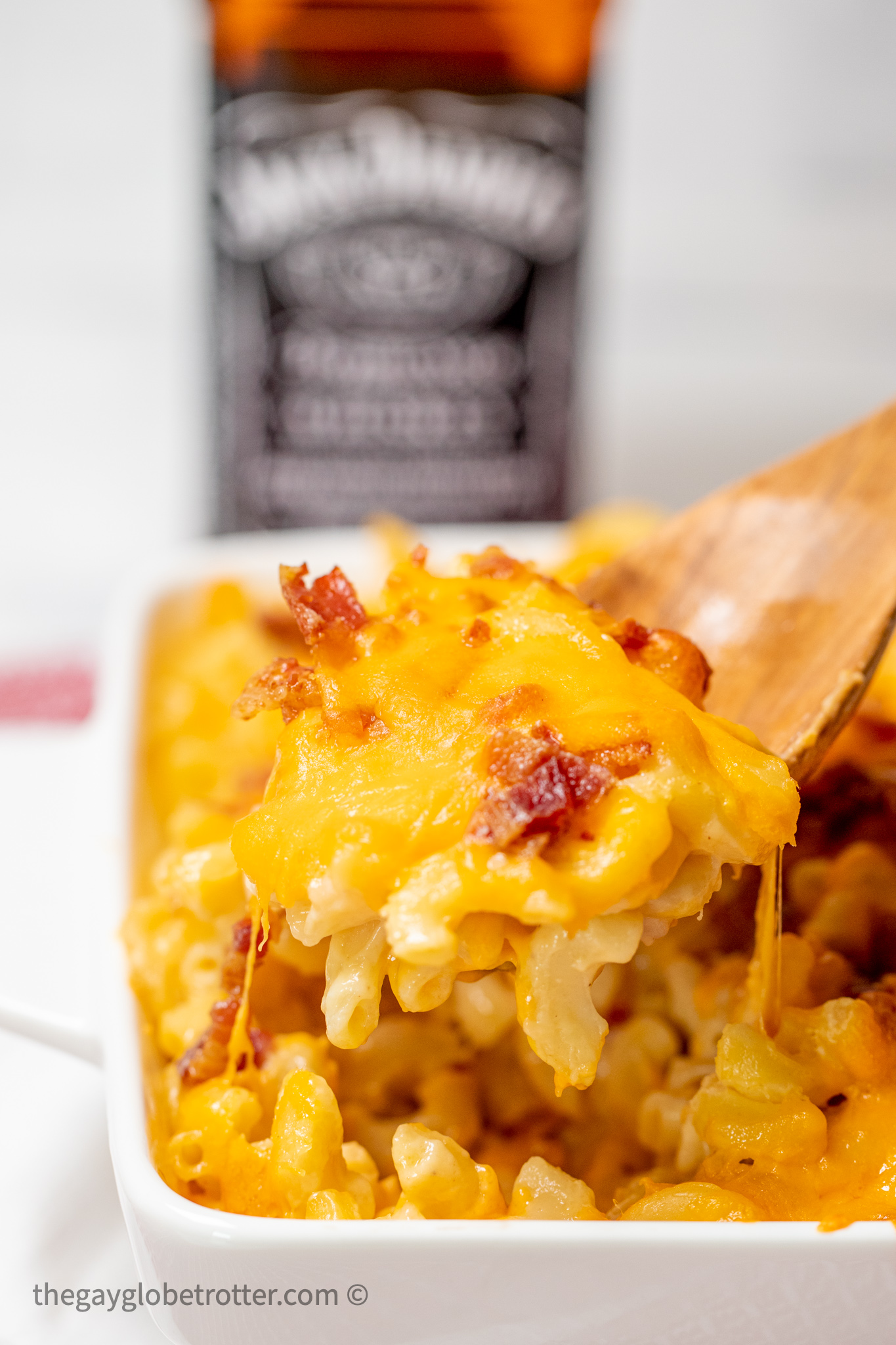 A spoon serving bacon bourbon mac and cheese.