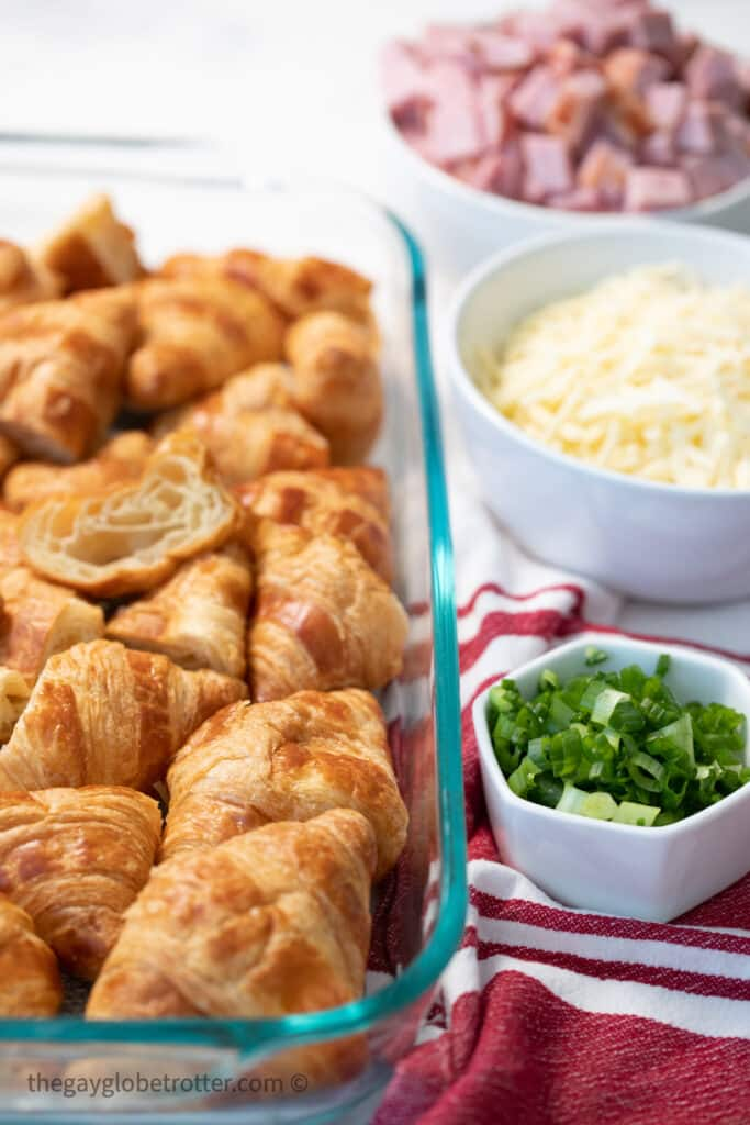 Croissants in a dish next to cubed ham, green onions, and cheese.