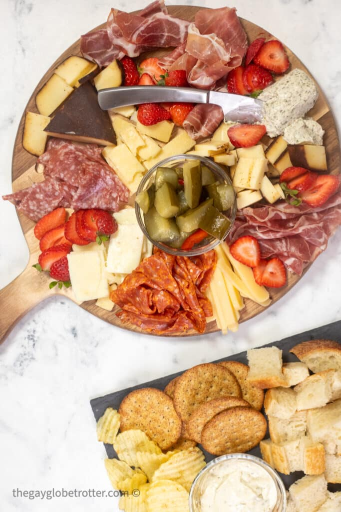 A charcuterie board filled with meat, cheese, berries, and crackers.