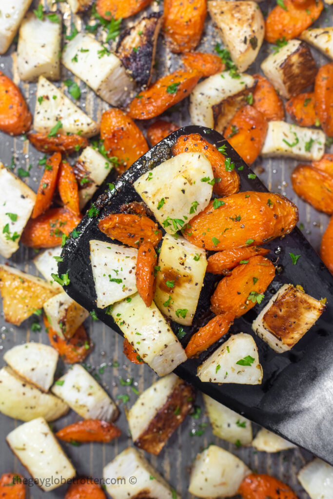 A spatula serving roasted turnips and carrots.