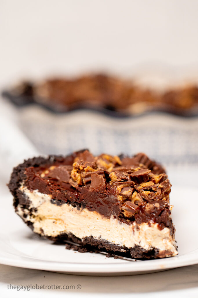 A slice of pie on a plate topped with peanut butter cups.