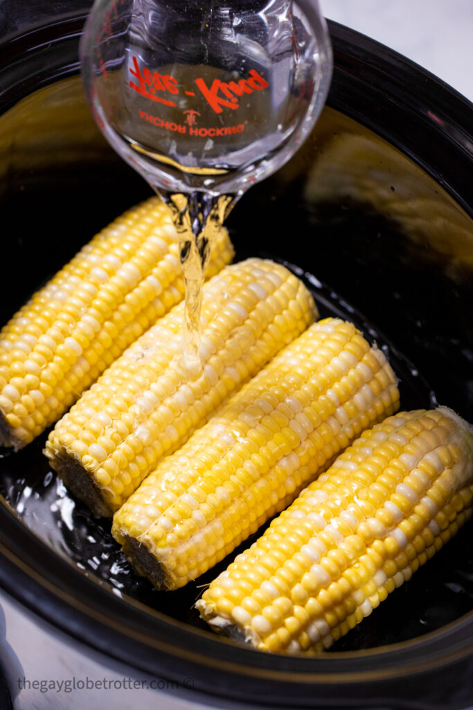 Corn arranged in a slow cooker while water is poured over it.