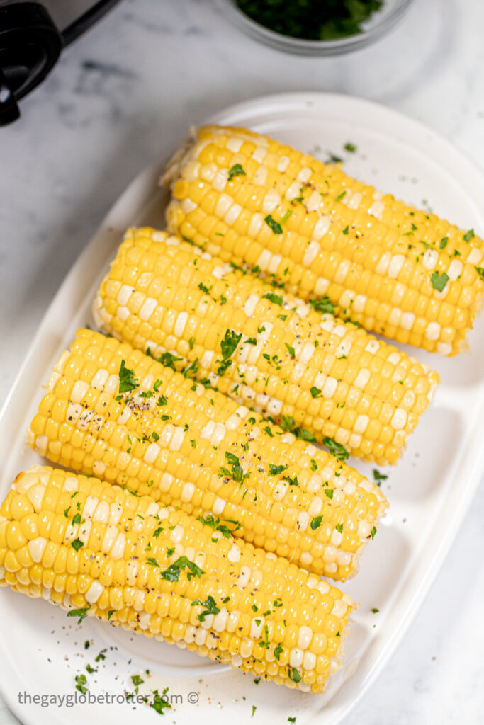 Corn in the cob on a platter garnished with parsley and butter.