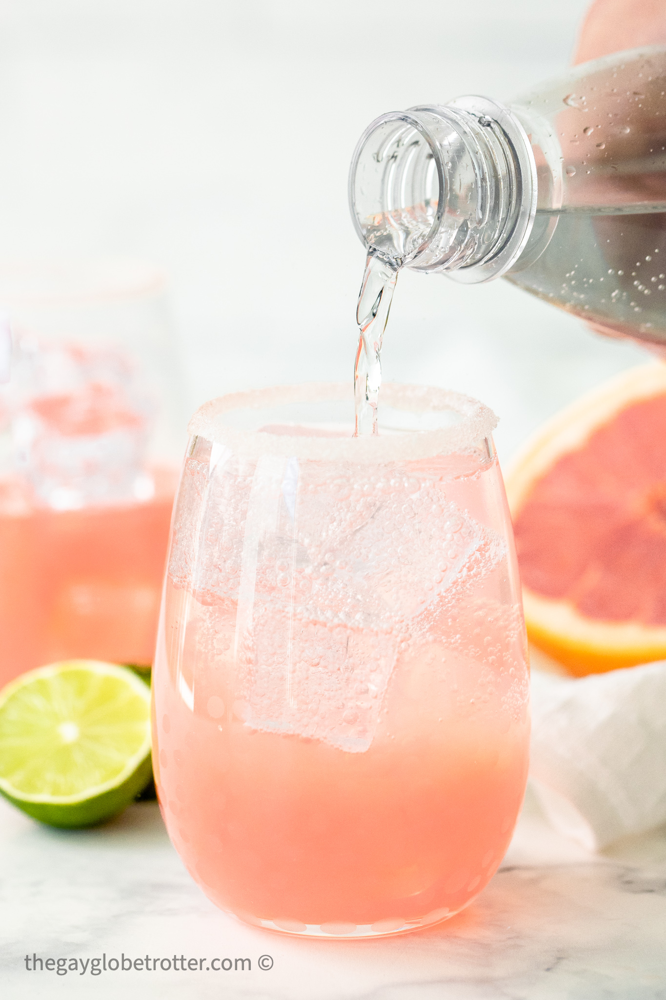 Soda water being poured into a paloma.