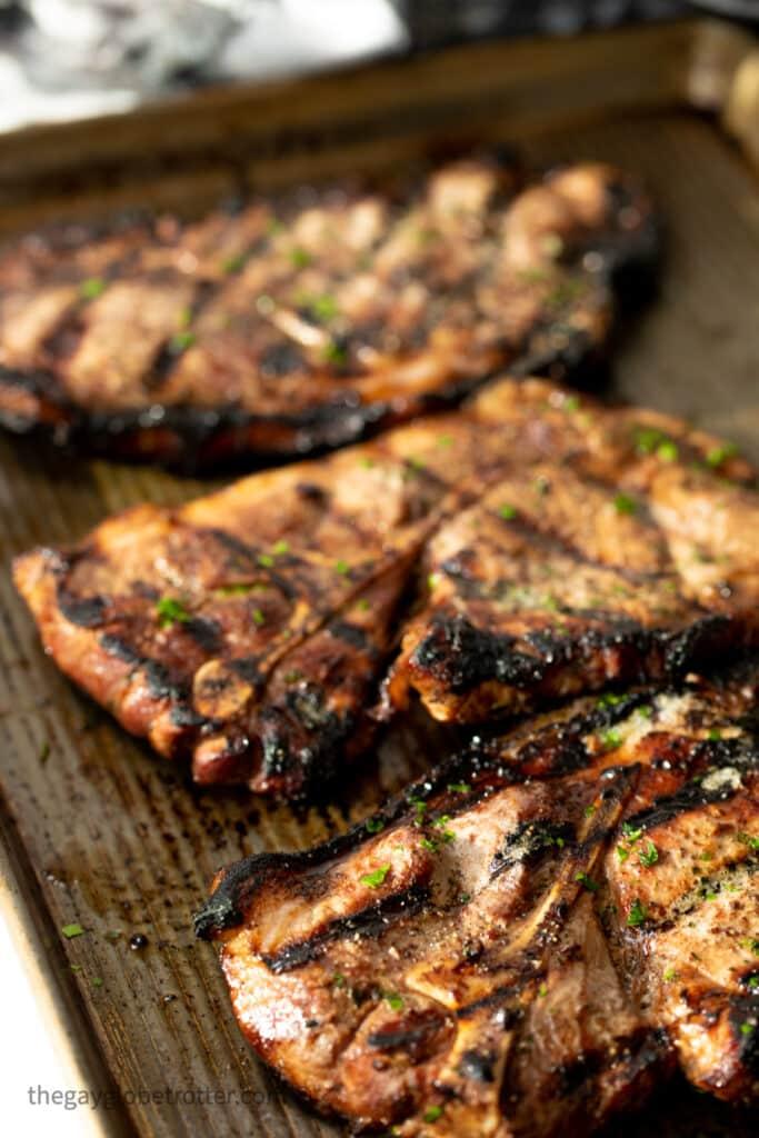 Grilled pork shoulder steaks garnished with parsley on a baking sheet.