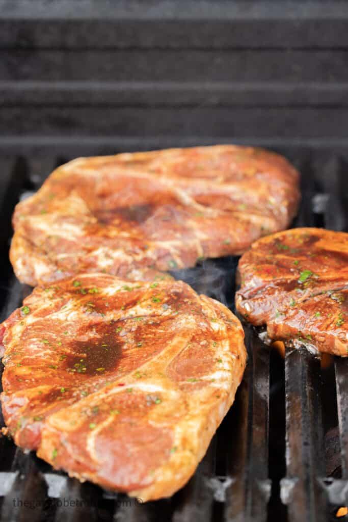 Three pork shoulder steaks on a grill.