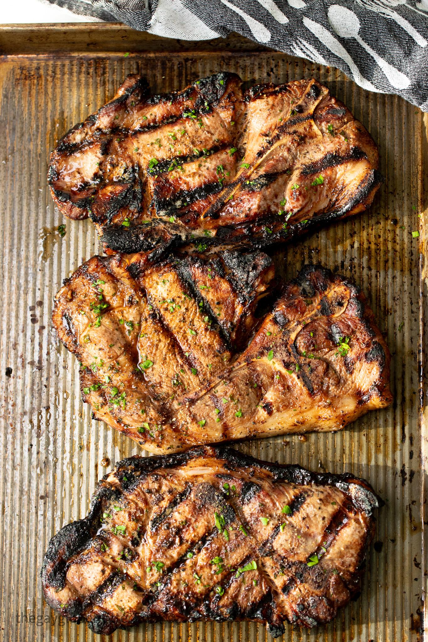 3 pork shoulder steaks on a baking sheet resting.