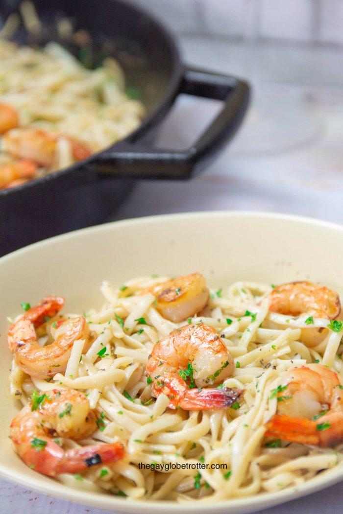 A bowl of shrimp scampi with pasta next to a pan with more shrimp scampi.