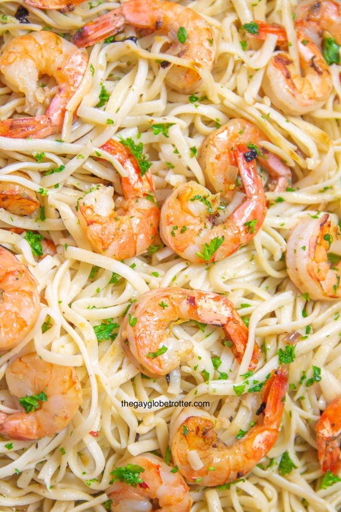 A close up of shrimp scampi with linguine noodles.