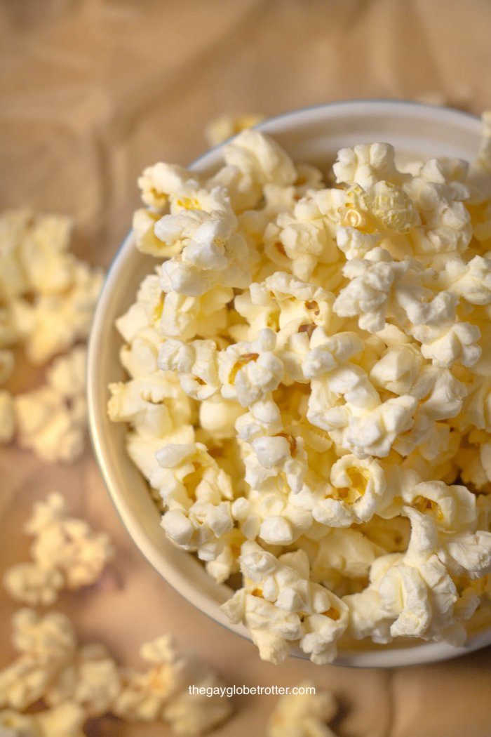 A bowl of kettle corn on a piece of parchment paper.