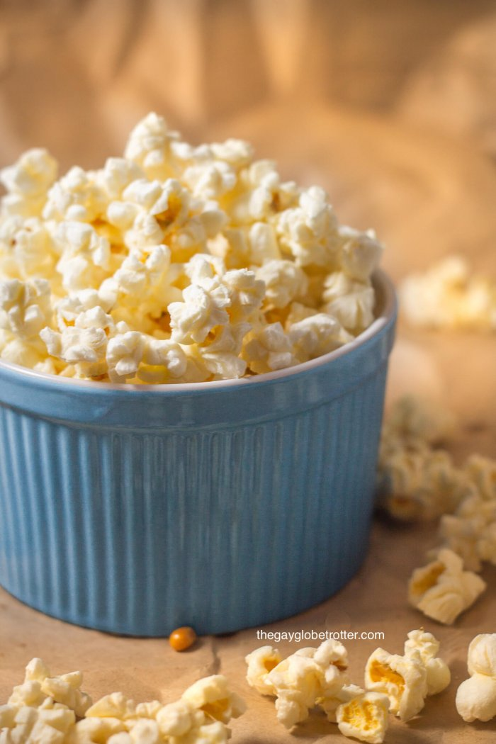 A blue bowl full of kettle corn with extra kettle corn around it.