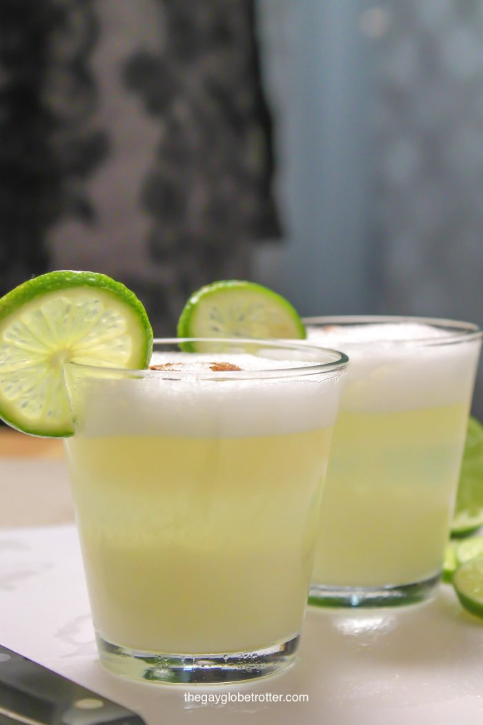 Peruvian pisco sours on a cutting board garnished with lime wedges.