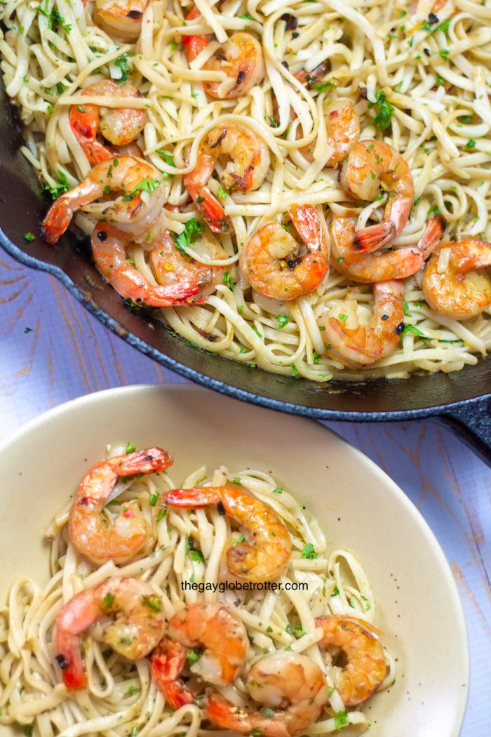 A bowl of shrimp scampi next to a pan full of more scampi.