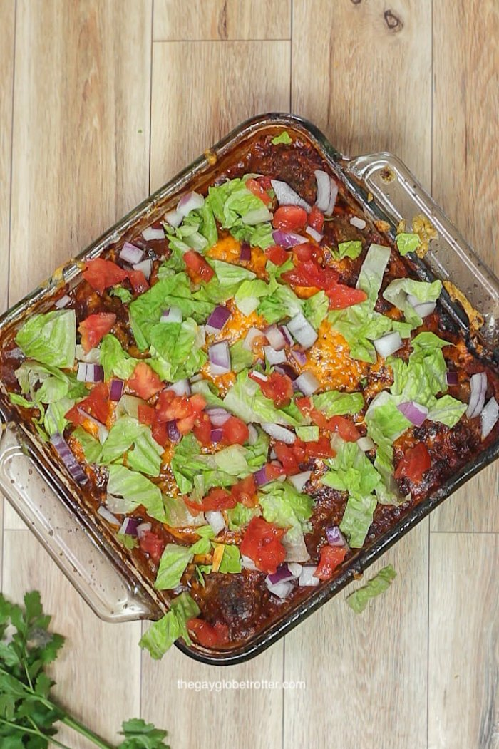 Taco meatball casserole in a baking dish topped with melted cheese, lettuce, tomatoes, and red onions.