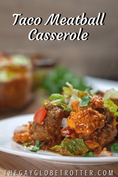 This easy taco meatball casserole is a fun and delicious meatball bake that is perfect for busy weeknights. Bake the taco meatballs smothered in taco sauce and cheese, then add your favorite toppings! #gayglobetrotter #taco #meatballcasserole #tacos #tacomeatballcasserole #tacomeatballs