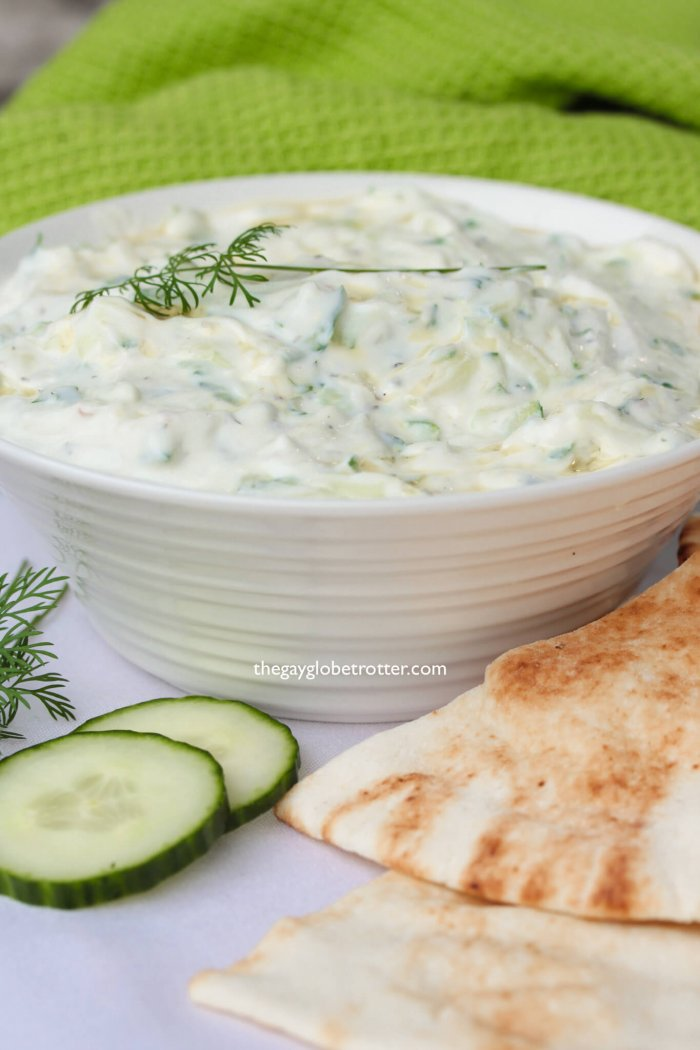 Homemade tzatziki with dill, pita bread, and cucumbers.