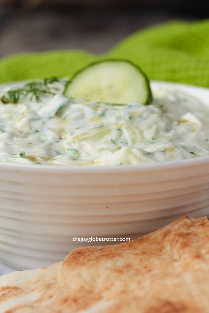 A bowl of homemade tzatziki with pita and cucumbers.